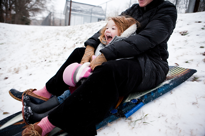 girl sledding with mother