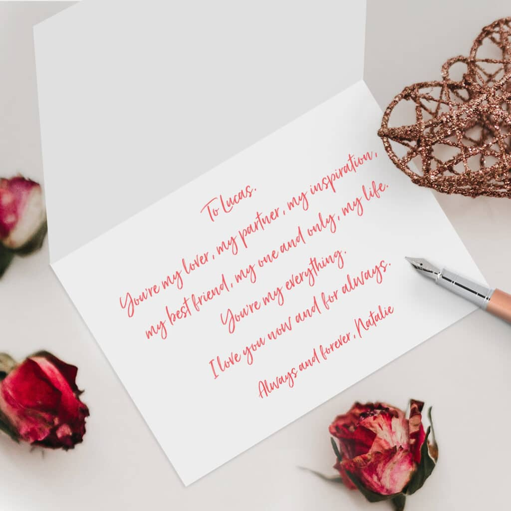 Card with handwritten message lying open on a table with pen and flower buds