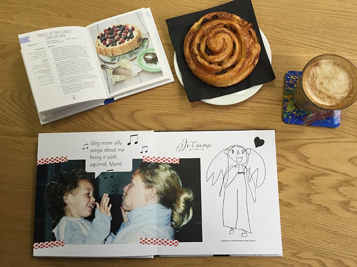 Photo book, recipe book, pastry and coffee on a table