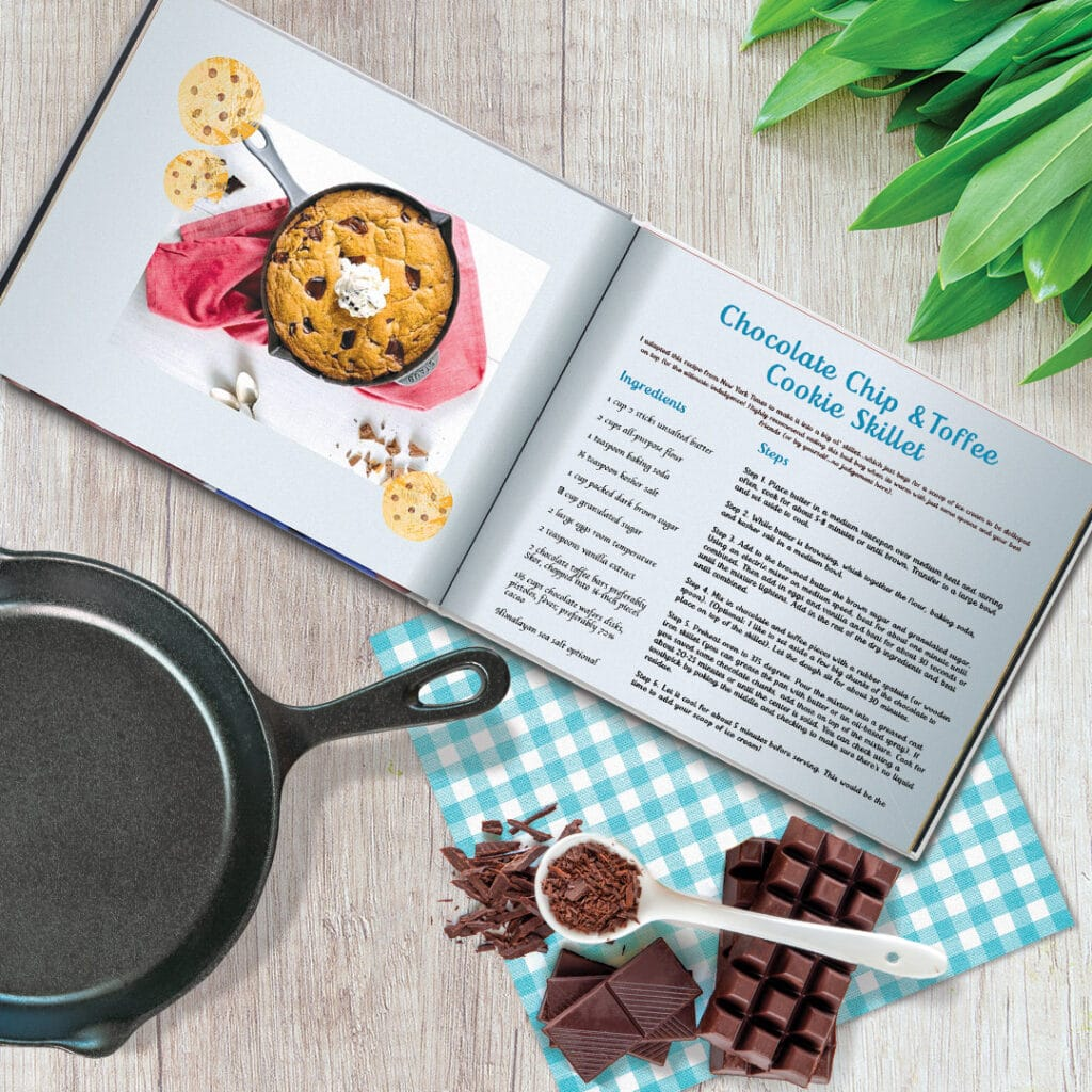 Recipe book, frying pan and chocolate on a table