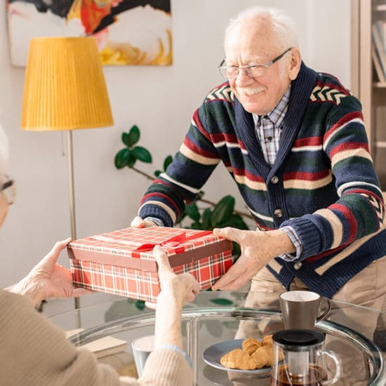 old man giving wife an anniversary gift
